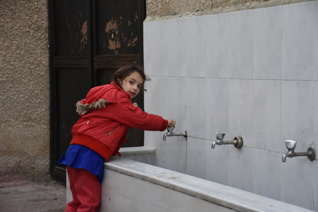 Bambina beve acqua dai rubinetti installati da Oxfam. Dania Kareh - Oxfam