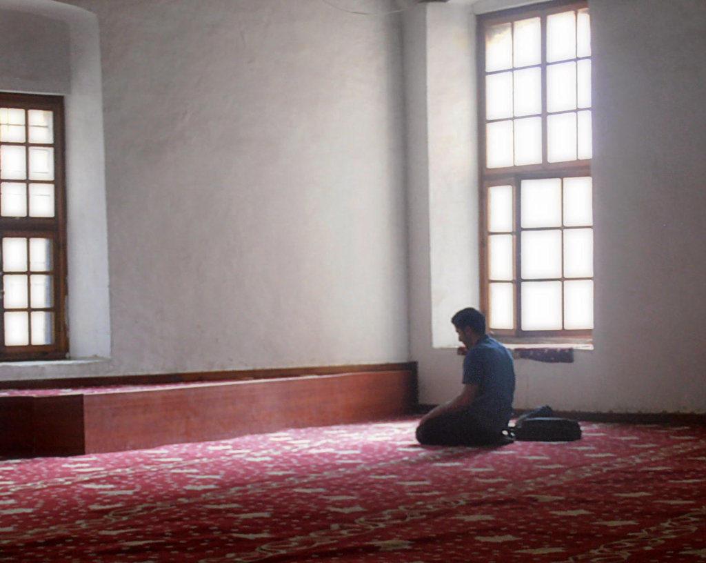 Un ragazzo prega trai raggi di luce della moschea di Selimiye Nicosia Cipro del Nord