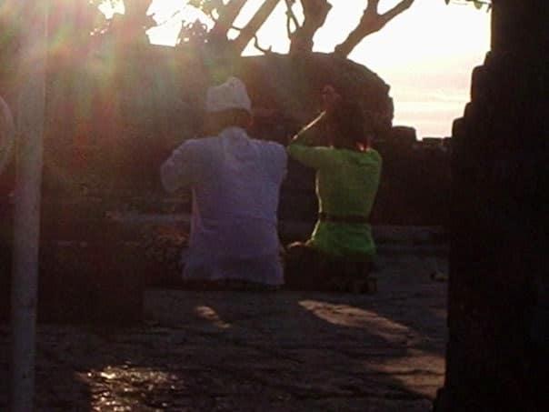 Un uomo e una donna pregano al tramonto nel tempio di Pura Luhur Ulu Watu, Bali, Indonesia