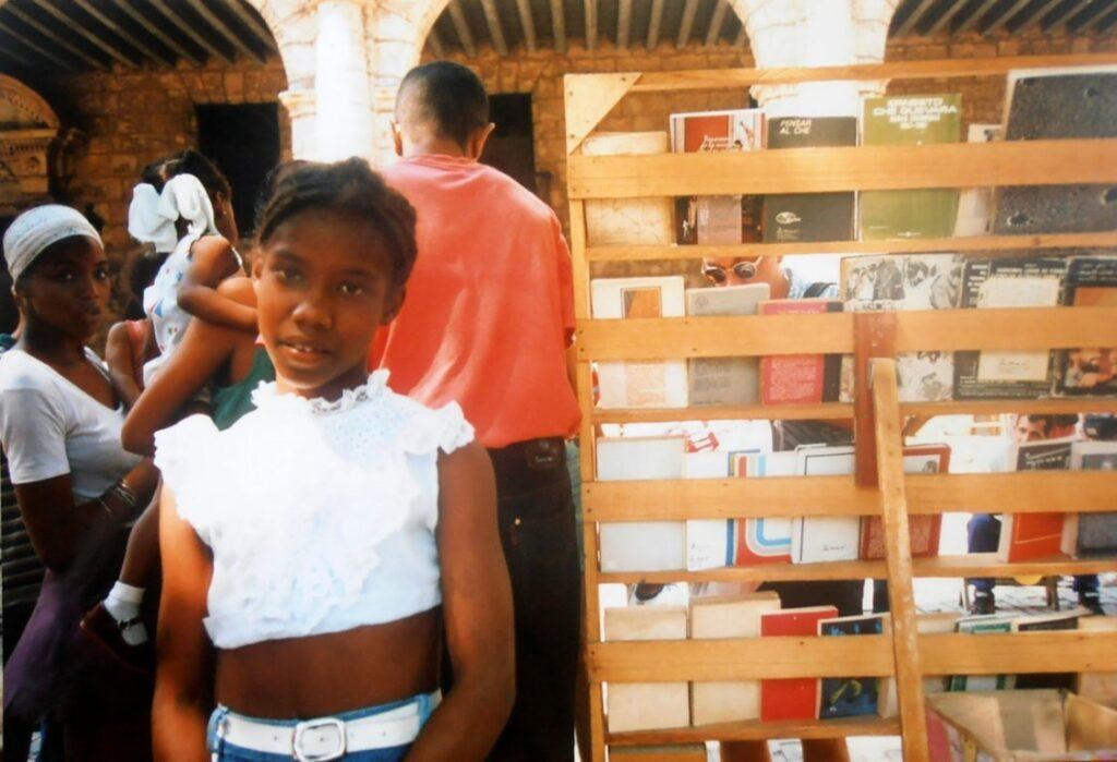 Una bambina posa vicino ad una bancarella di libri a l'Habana, Cuba
